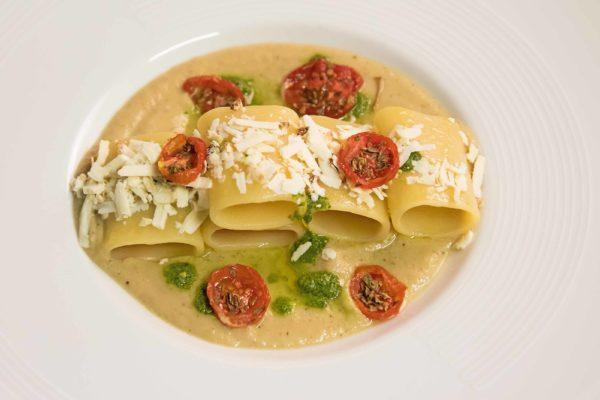 Paccheri di Gragnano con crema di melanzane montata all'olio evo Zenia, pomodorini confit, basilico liquido e ricotta salata infornata